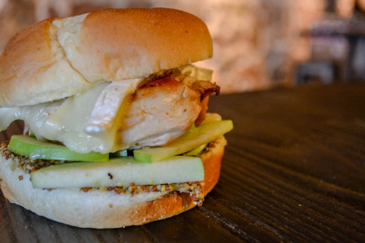 <h5>Chicken and Brie Sandwich</h5><p>Featuring chef's signature cider-brined chicken, brie, dijon, and fresh apples on a brioche bun</p>