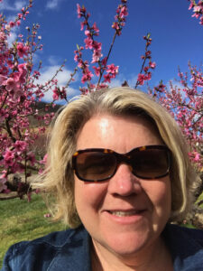 Cynthia Chiles with peach tree blossoms