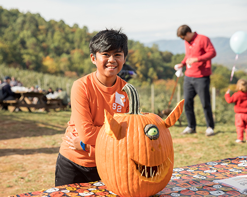 Kid and a carved pumpkin during an event at Carter Mountain Orchard