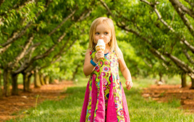 Girl in peach orchard with ice cream