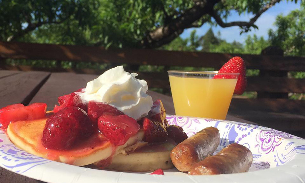 Pancake breakfast with strawberries, sausage, and cider mimosa
