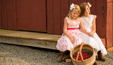 Girls at the Spring Valley Orchard store with a basket of cherries