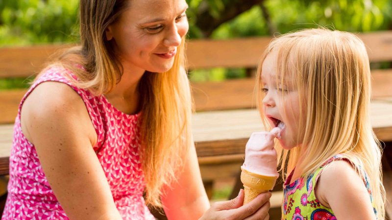 mother feeding ice cream to daughter