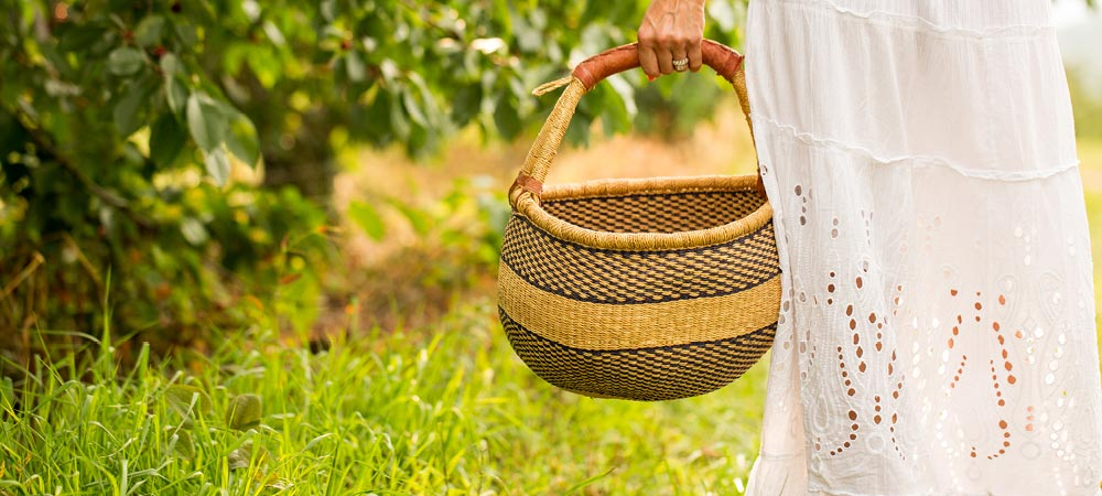 Woman holding basket in orchard