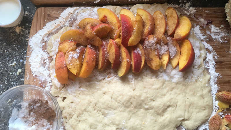 Rolled out dough with peach slices
