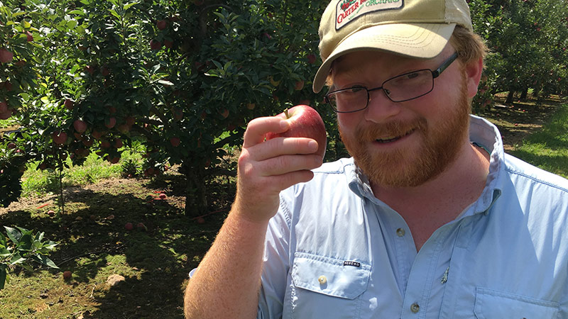 Farmer Henry holding up a red apple
