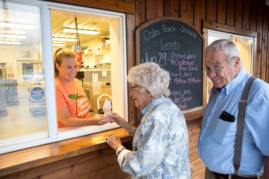 young woman serves ice cream to older couple