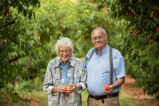 Ruth and Henry Chiles holding peaches in the orchard