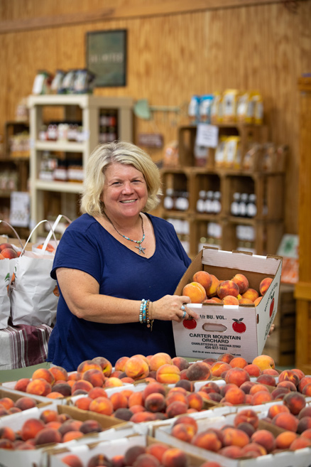 Cynthia Chiles holding crate of peaches
