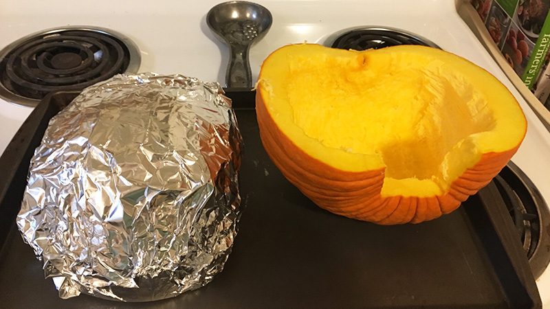 cut pumpkin covered in foil for oven roasting