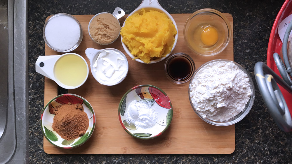 Ingredients for pumpkin bread include white and brown sugar, egg, coconut oil, vanilla extract, sour cream, pumpkin puree, cinnamon, pumpkin pie spice, and ground nutmeg