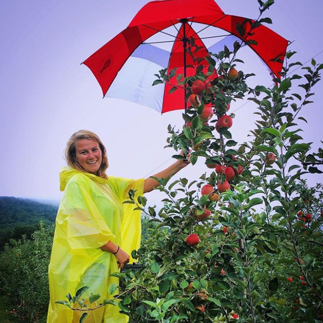 Ally Chiles with an umbrella over a peach tree during Florence tropical storm in 2018