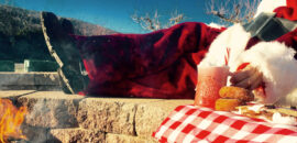 Santa sitting by the firepit with donuts and hot apple cider