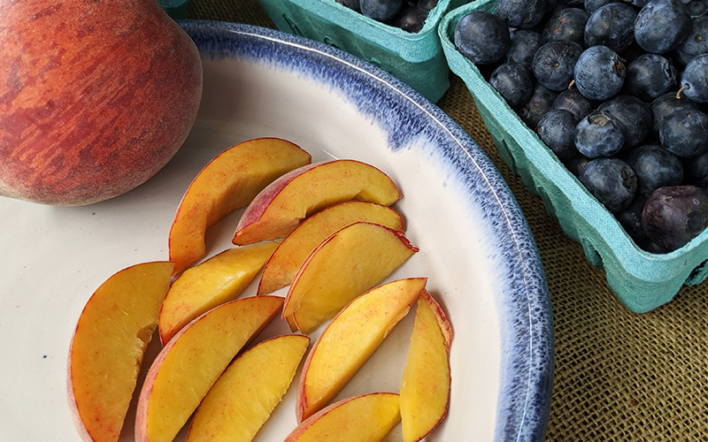 Sliced peaches on a pottery plate next to blueberries