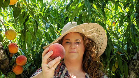 Lizzy Chiles holding peaches in front of peach tree at Chiles