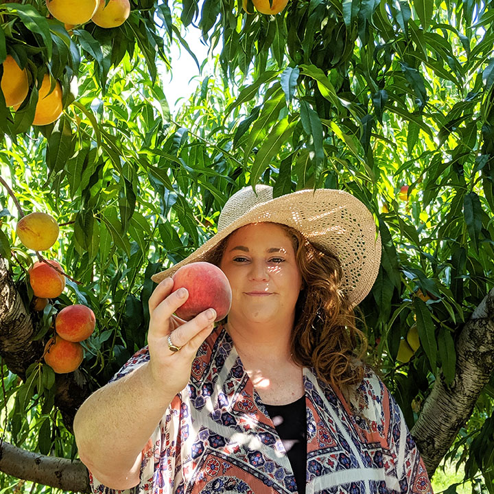 Lizzy Chiles holds a free peach at the Orchard in Virginia