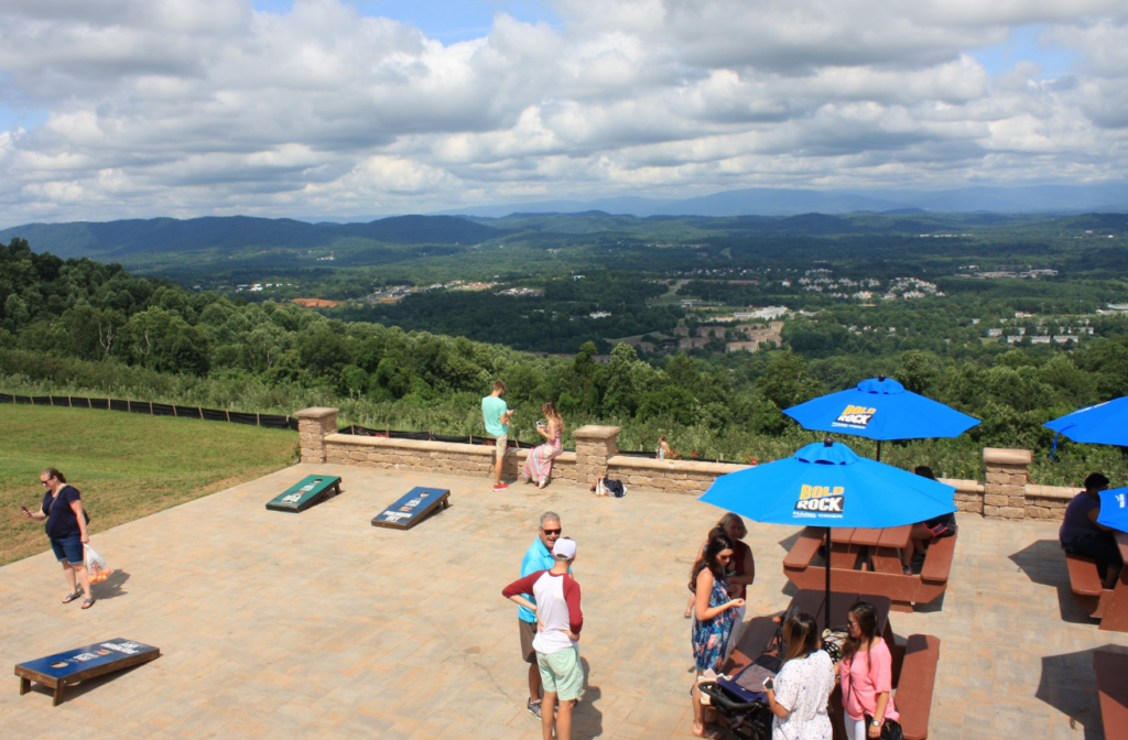 Stone patio at Carter Mountain Orchard with picnic tables and corn hole boards