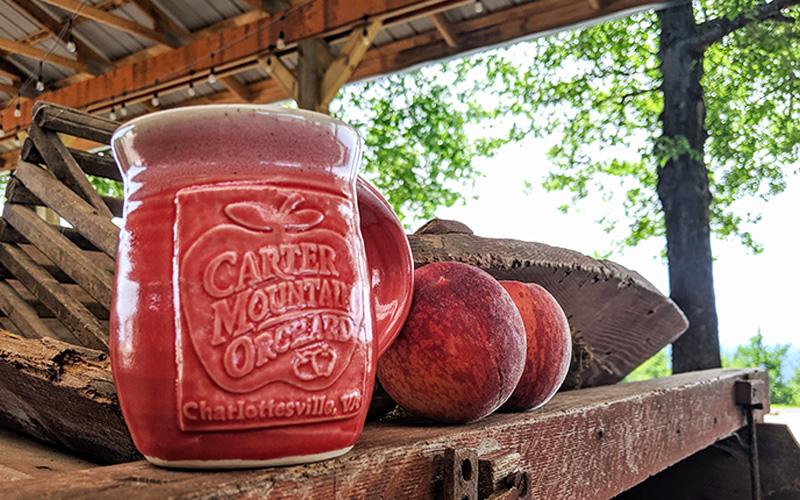 Carter Mountain Orchard handmade ceramic mug and fresh peaches