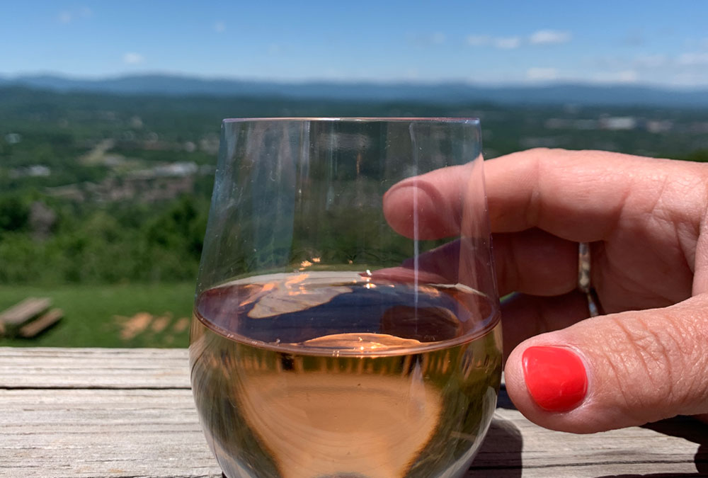Carter Mountain Wine Rose 2020 on a wooden deck with a hand