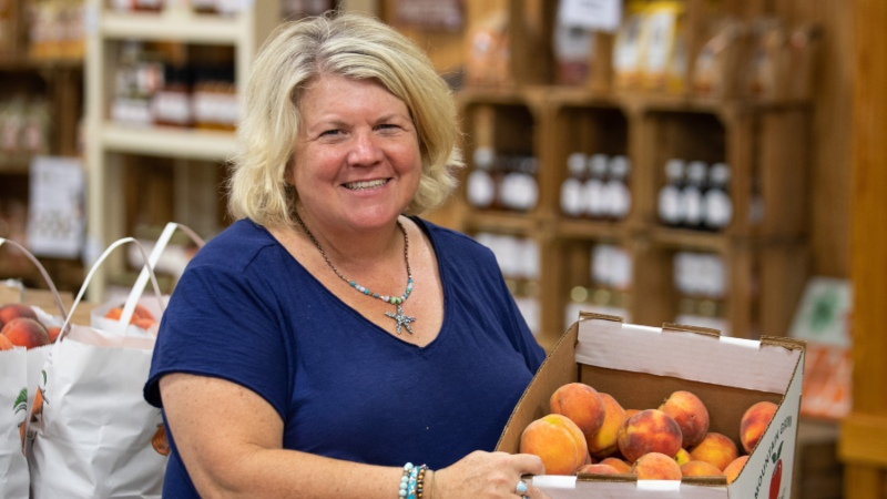 Cynthia Chiles holding a box of peaches at Chiles Peach Orchard