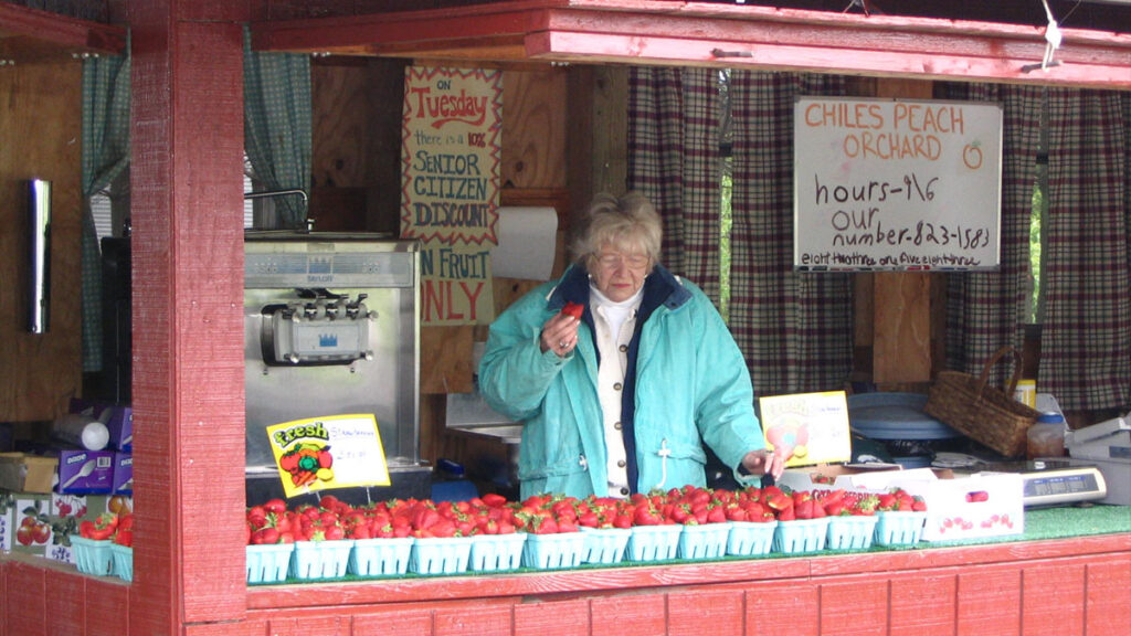 Ruth Chiles at farm stand with strawberries